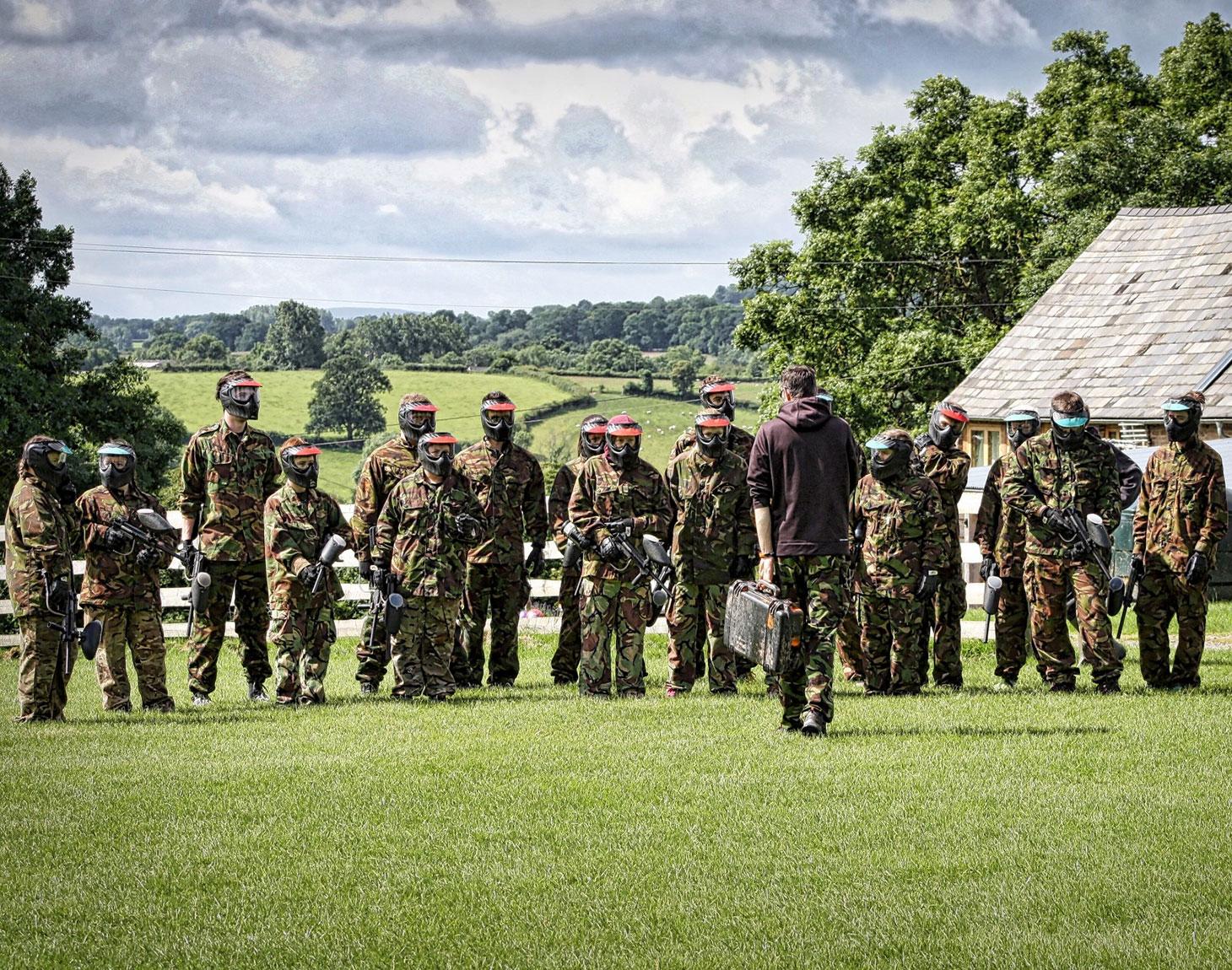 Grupo de pessoas com armamento e roupas para paintball em um gramado verde.