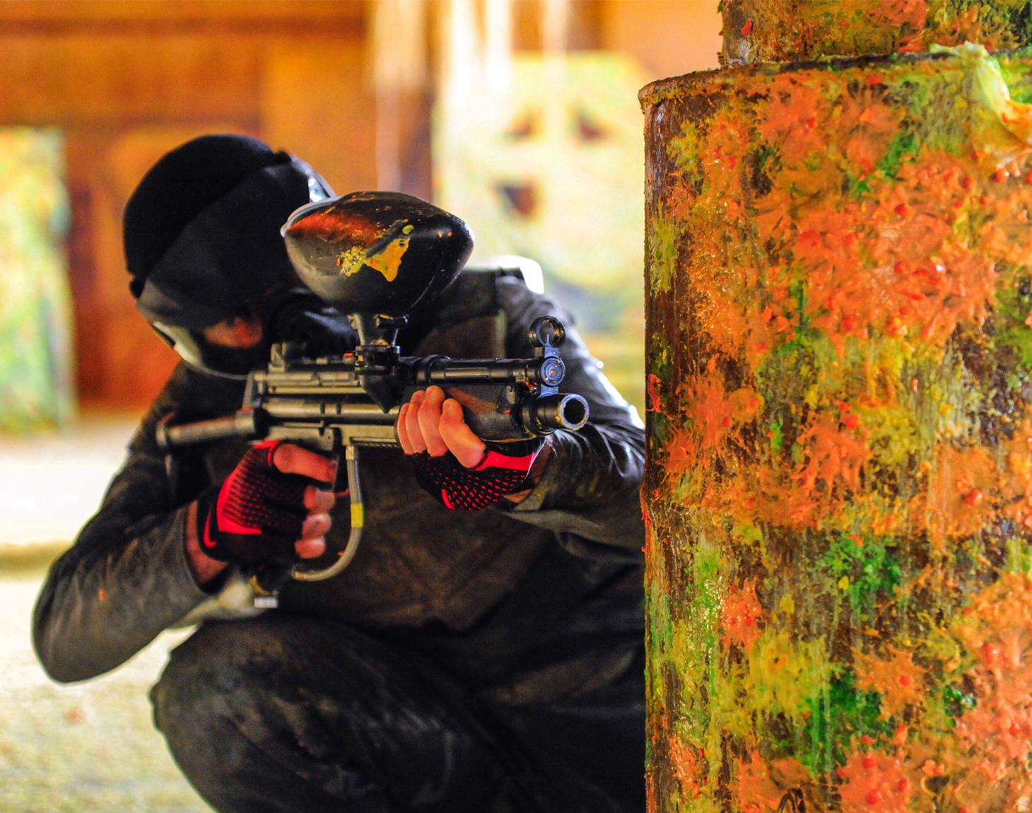 Homem de roupa preta atrás de um barril com marcas de tiros de paintball apontando arma de paintball.